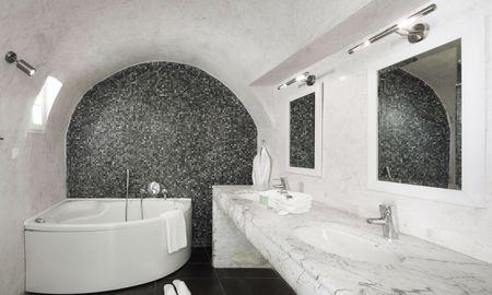 Habitación Petit Suite con jacuzzi privado climatizado al aire libre. - Petit Palace Suites - Santorini